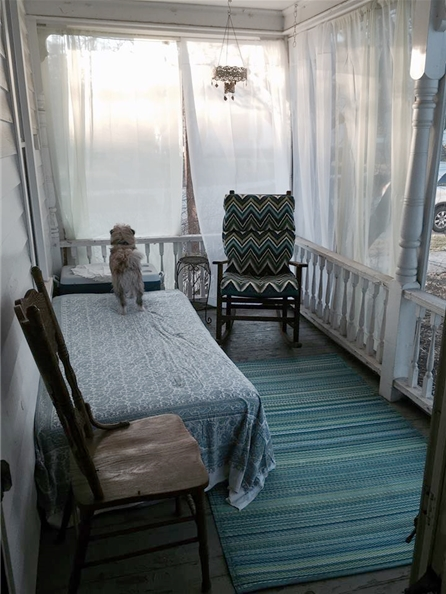Inspirational image of porch with day bed, rug, 2 chairs and a samll chandelier